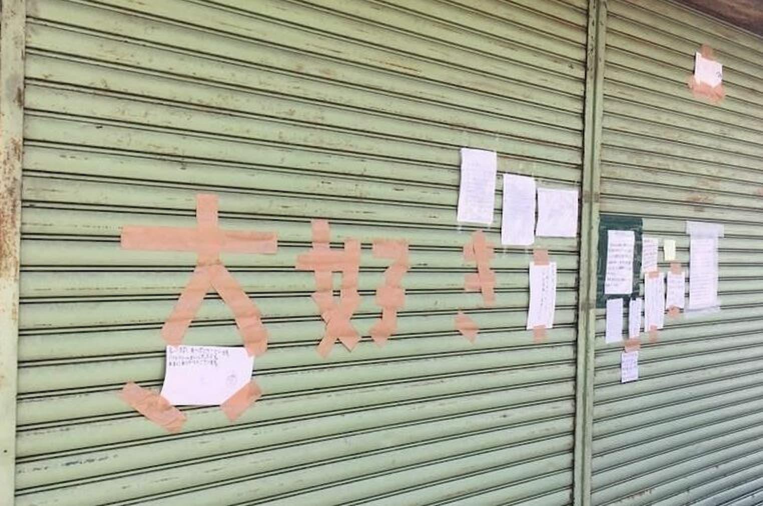 廃業後シャッターに貼られたファンからのメッセージ。店を愛する客が味と記憶を承継